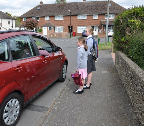 a stranger in a car talking to school children